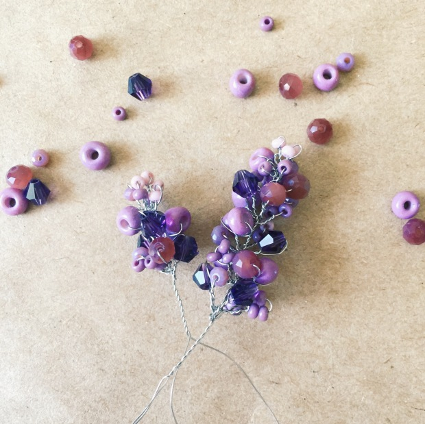 Purple flowers from beads and some lilac beads on the beige paper