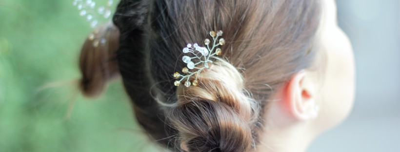 Decorative hair pins from crystals in hair buns close up blurred background