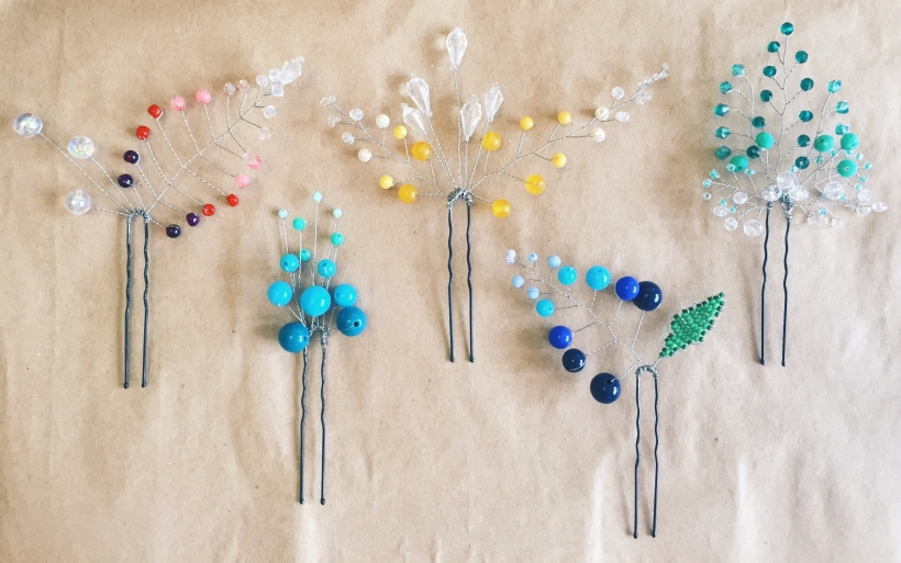 5 beautiful hairpins handmade colorful from beads and crystals on beige background