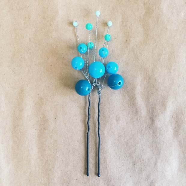 Cute gradient hairpin from light blue, blue and dark blue beads on the beige background