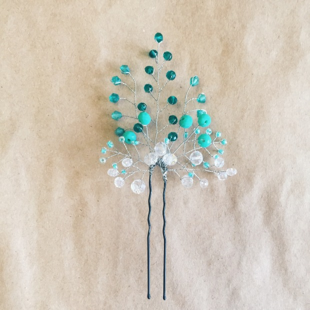 A hairpin from dark and light turquoise color beads on beige background