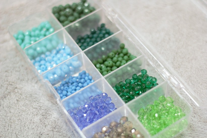 Different shades of green crystals and blue crystals sparkly in a container on a light grey background