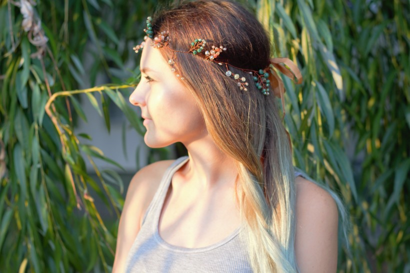 Beautiful green and gold bohemian hair accessory in the hair of the girl under the sunlight