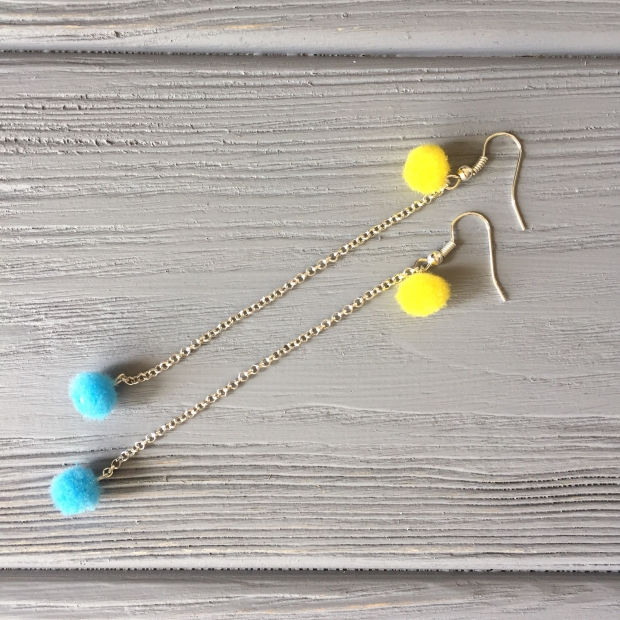 Two pompoms attached to the chain of future earrings
